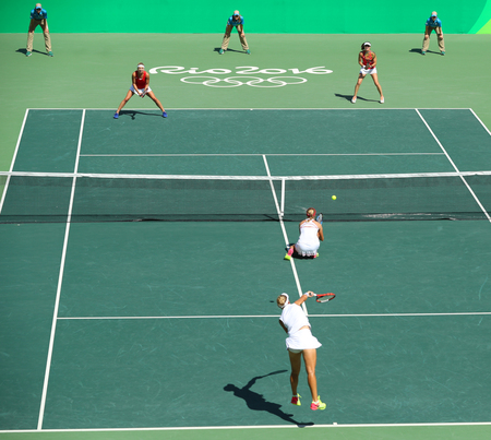 olympic symbol: RIO DE JANEIRO, BRAZIL - AUGUST 14, 2016:E. Makarova and E. Vesnina of Russia(in white) and T. Bacsinszky and M. Hingis of Switzerland in action during womens doubles final of the Rio 2016 Olympics Editorial