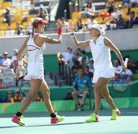 doubles: RIO DE JANEIRO, BRAZIL - AUGUST 14, 2016: Ekaterina Makarova (L) and Elena Vesnina of Russia in action during womens doubles final of the Rio 2016 Olympic Games at the Olympic Tennis Centre Editorial
