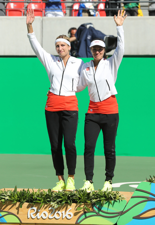RIO DE JANEIRO, BRAZIL - AUGUST 14, 2016: Silver medalists team Switzerland Timea Bacsinszky (L) and Martina Hingis during medal ceremony after tennis womens doubles final of the Rio 2016 Olympics