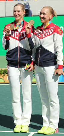 RIO DE JANEIRO, BRAZIL - AUGUST 14, 2016: Olympic champions team Russia Ekaterina Makarova (L) and Elena Vesnina during medal ceremony after tennis womens doubles final of the Rio 2016 Olympic Games Editorial