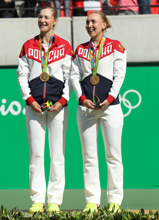 olympic symbol: RIO DE JANEIRO, BRAZIL - AUGUST 14, 2016: Olympic champions team Russia Ekaterina Makarova (L) and Elena Vesnina during medal ceremony after tennis womens doubles final of the Rio 2016 Olympic Games Editorial
