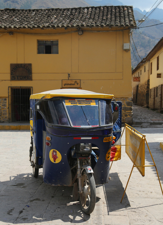 conquered: OLLANTAYTAMBO, PERU - OCTOBER 1, 2016: Auto rickshaw in the street of Ollantaytambo, Peru. Ollantaytambo was the royal estate of Emperor Pachacuti who conquered the region.