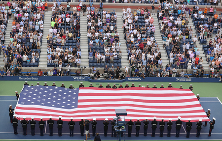 unfurling: NEW YORK- SEPTEMBER 11, 2016: US Marine Corps unfurling American Flag during the opening ceremony of the US Open 2016 mens final at Billie Jean King National Tennis Center in New York