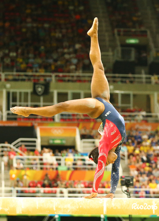 RIO DE JANEIRO, BRAZIL AUGUST 7, 2016: Olympic champion Simone Biles of United States competing on the balance beam at womens all-around gymnastics qualification at Rio 2016 Olympic Games