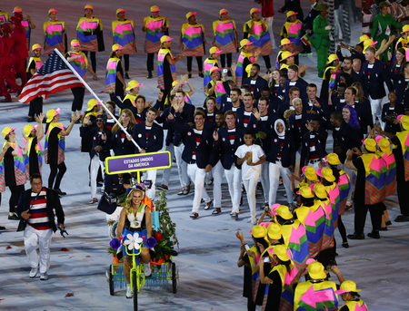 the olympic rings: RIO DE JANEIRO, BRAZIL - AUGUST 5, 2016: Olympic champion Michael Phelps carrying the United States flag leading the Olympic team USA in the Rio 2016 Opening Ceremony at Maracana Stadium