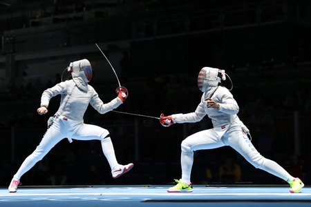 olympic ring: RIO DE JANEIRO, BRAZIL - AUGUST 13, 2016: Ibtihaj Muhammad of United States R and Sofya Velikaya of Russia compete in the Women`s Sabre Team of the Rio 2016 Olympic Games at Carioca Arena 3