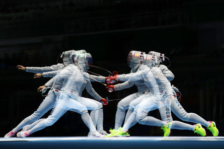 muhammad: RIO DE JANEIRO, BRAZIL - AUGUST 13, 2016: Ibtihaj Muhammad of United States R and Sofya Velikaya of Russia compete in the Women`s Sabre Team of the Rio 2016 Olympic Games at Carioca Arena 3