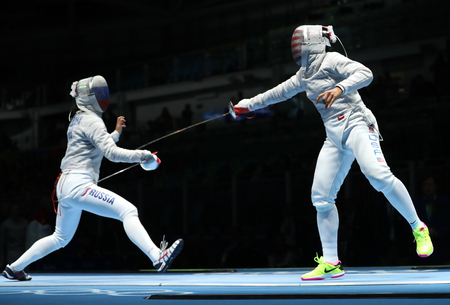 muhammad: RIO DE JANEIRO, BRAZIL - AUGUST 13, 2016: Ibtihaj Muhammad of United States (R) and Sofya Velikaya of Russia compete in the Womens Sabre Team of the Rio 2016 Olympic Games at Carioca Arena 3 Editorial