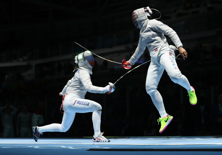 RIO DE JANEIRO, BRAZIL - AUGUST 13, 2016: Ibtihaj Muhammad of United States (R) and Sofya Velikaya of Russia compete in the Womens Sabre Team of the Rio 2016 Olympic Games at Carioca Arena 3 Editorial