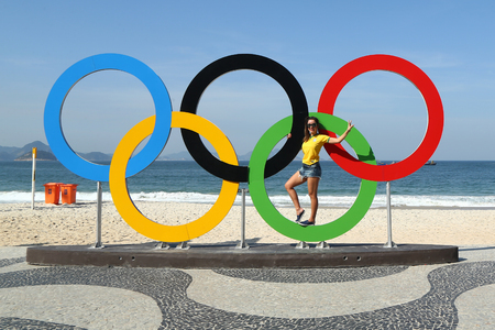 RIO DE JANEIRO, BRAZIL - AUGUST 6, 2016: Brazilian tourist taking picture of Olympic Rings at Copacabana Beach in Rio de Janeiro
