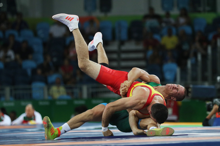 RIO DE JANEIRO, BRAZIL - AUGUST 14, 2016:Wrestler Peter Basci of Hungary (in green) and  Carlos Andres Munoz Jaramillo of Columbia during Mens Greco-Roman 75 kg Qualification of the Rio 2016 Olympics Editorial