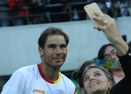 champion spain: RIO DE JANEIRO, BRAZIL - AUGUST 12, 2016: Olympic champion Rafael Nadal of Spain taking selfie with tennis fan after mens singles semifinal of the Rio 2016 Olympic Games at the Olympic Tennis Centre