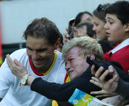champion spain: RIO DE JANEIRO, BRAZIL - AUGUST 12, 2016: Olympic champion Rafael Nadal of Spain with tennis fan after mens singles semifinal of the Rio 2016 Olympic Games at the Olympic Tennis Centre