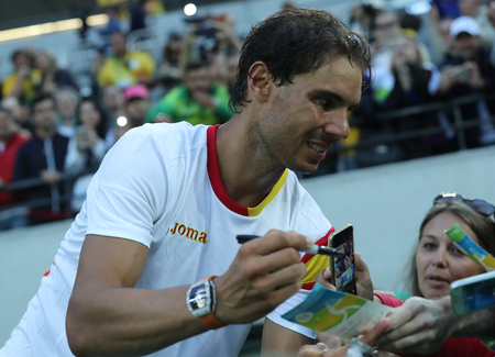 champion spain: RIO DE JANEIRO, BRAZIL - AUGUST 12, 2016: Olympic champion Rafael Nadal of Spain gives autographs after mens singles semifinal of the Rio 2016 Olympic Games at the Olympic Tennis Centre