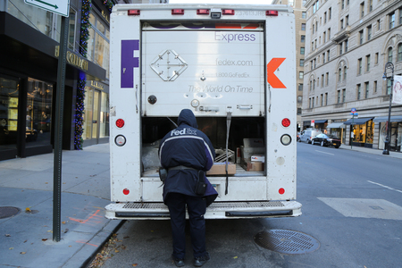 delivers: NEW YORK - DECEMBER 15, 2016: FedEx driver delivers packages during Holidays season in Manhattan. Editorial