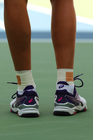 billie: NEW YORK - AUGUST 29, 2016: Professional tennis player Polona Hercog of Slovenia wears custom ASICS tennis shoes during match at US Open 2016 at Billie Jean King National Tennis Center in New York