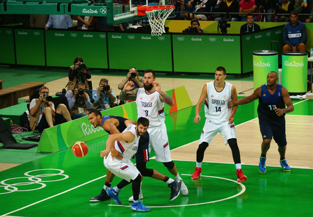 serbia: RIO DE JANEIRO, BRAZIL - AUGUST 10, 2016: Team Serbia (in white) and team France in action during group A basketball match of the Rio 2016 Olympic Games at Carioca Arena 1