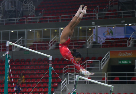 olympic ring: RIO DE JANEIRO, BRAZIL AUGUST 4, 2016: Olympic champion Gabby Douglas  of United States practices on the uneven bars before womens all-around gymnastics at Rio 2016 Olympic Games