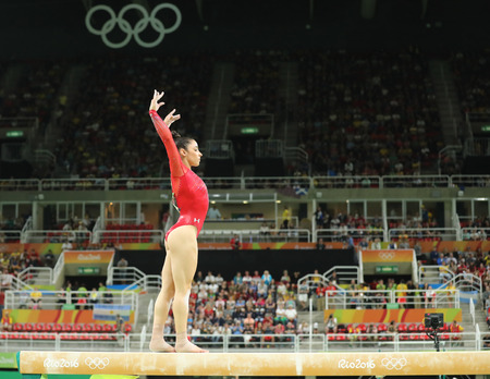 RIO DE JANEIRO, BRAZIL - AUGUST 11, 2016: Olympic champion Aly Raisman of United States competes on the balance beam at women's all-around gymnastics at Rio 2016 Olympic Games Imagens - 71005195