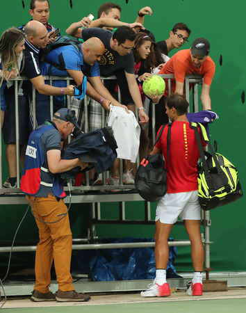 olympic ring: RIO DE JANEIRO, BRAZIL - AUGUST 7, 2016: Olympic champion Rafael Nadal of Spain signs autographs after mens singles first round match of the Rio 2016 Olympic Games at the Olympic Tennis Centre