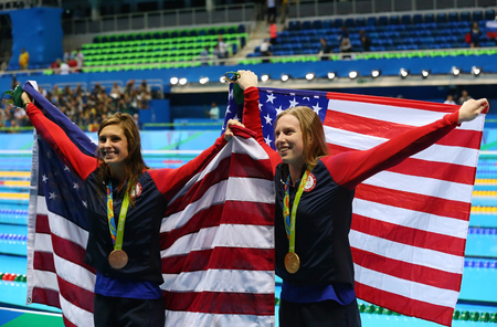 olympic ring: RIO DE JANEIRO, BRAZIL - AUGUST 8, 2016: Catherine Meili (L) and Lilly King of the United States celebrate after Womens 100m Breaststroke Final of the Rio 2016 Olympic Games
