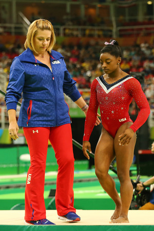 RIO DE JANEIRO, BRAZIL - AUGUST 15, 2016: Olympic champion Simone Biles (R) and coach Aimee Boorman before final competition on the balance beam womens artistic gymnastics at Rio 2016 Olympic Games