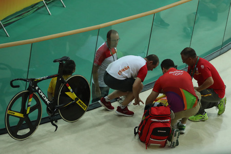 RIO DE JANEIRO, BRAZIL - AUGUST 13, 2016: Medics help cyclist Tania Calvo of Spain after her crash during Rio 2016 Olympics womens keirin first round heat 2 at the Rio Olympic Velodrome