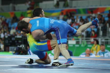 janeiro: RIO DE JANEIRO, BRAZIL - AUGUST 14, 2016: Wrestlers Ibragim Labazanov of Russia (in  blue) and Almat Kebispayev of Kazakhstan during Mens Greco-Roman 59 kg Qualification of the Rio 2016 Olympics
