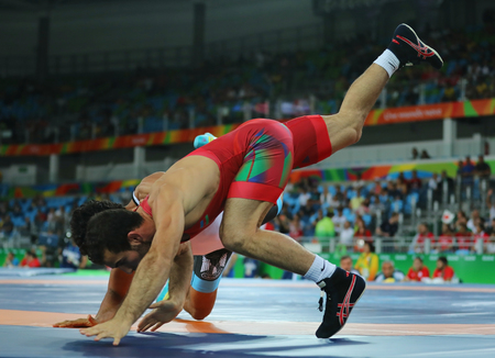 RIO DE JANEIRO, BRAZIL - AUGUST 14, 2016: Wrestlers Elvin Mursaliyev of Azerbaijan  (in red) and Mahmoud Fawzy of Egypt in action during Mens Greco-Roman 75 kg Qualification of the Rio 2016 Olympics Editorial