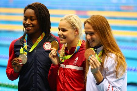 piscina olimpica: RIO DE JANEIRO, BRASIL - 13 DE AGOSTO DE 2016: Simone Manuel (L) USA, Pernille Blume Dinamarca y Aliaksandra Herasimenia BLR durante la ceremonia de medallas después de los 50 metros libres femeninos de los Juegos Olímpicos Rio 2016
