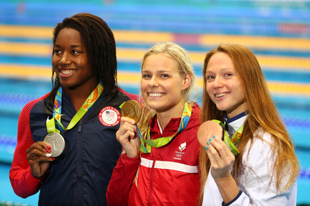 olympic symbol: RIO DE JANEIRO, BRAZIL - AUGUST 13, 2016:Simone Manuel (L) USA, Pernille Blume Denmark and Aliaksandra Herasimenia BLR during medal ceremony after Womens 50 metre freestyle of the Rio 2016 Olympics