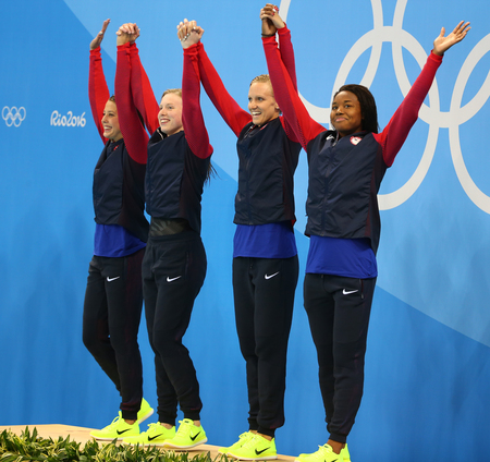 RIO DE JANEIRO, BRAZIL - AUGUST 13, 2016:Champions team USA Womens 4 × 100m medley relay Kathleen Baker (L) Lilly King, Dana Vollmer and Simone Manuel celebrate victory at the Rio 2016 Olympic Games