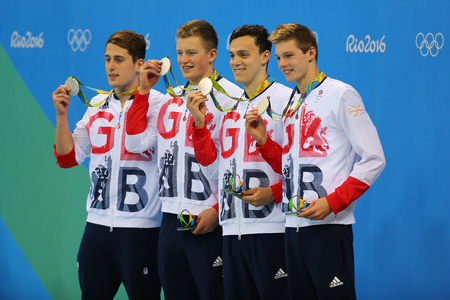 RIO DE JANEIRO, BRAZIL - AUGUST 13, 2016: Great Britain Mens 4x100m medley relay team Chris Walker-Hebborn, Adam Peaty, James Guy, Duncan Scott during medal ceremony at the Rio 2016 Olympic Games