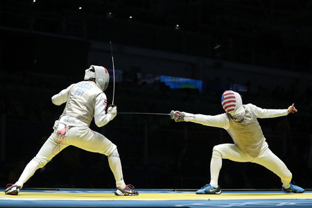 RIO DE JANEIRO, BRAZIL - AUGUST 12, 2016: Fencer of United States team (R) competes against team Egypt fencer in the Mens team foil of the Rio 2016 Olympic Games at the Carioca Arena 3