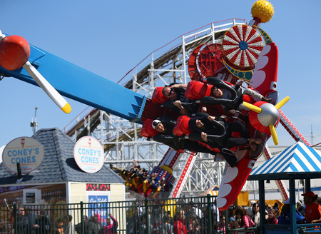 BROOKLYN, NEW YORK - APRIL 13, 2017: Air race ride in Coney Island Luna Park. Riders pilot their own planes around a control tower in this spinning ride. Air Race made its world debut at Luna Park Editorial