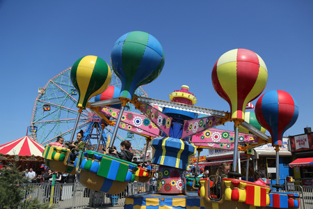 BROOKLYN, NEW YORK, APRIL 13, 2017: Kids ride at Coney Island Luna Park. Coney Island Luna Park was destroyed by fire in 1944, then reopened in 2010