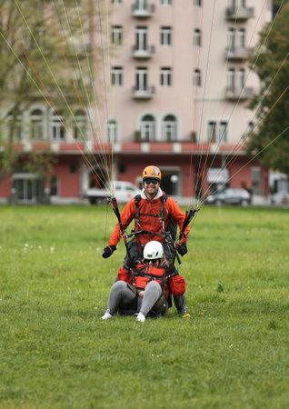 INTERLAKEN, SWITZERLAND - MAY 4, 2017: Tandem paragliding landing after flight over the Swiss Alps in Interlaken, Switzerland Editorial