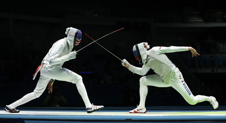 RIO DE JANEIRO, BRAZIL - AUGUST 12, 2016: Fencer of Team USA (L) competes against Team Russia fencer in the Mens team foil of the Rio 2016 Olympic Games at the Carioca Arena 3 Editorial