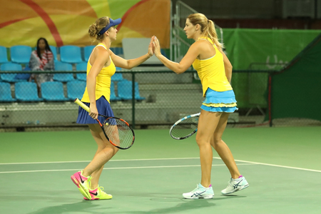RIO DE JANEIRO, BRAZIL - AUGUST 7, 2016: Tennis players Elina Svitolina (L) and Olga Savchuk of Ukraine in action during doubles first round match of the Rio 2016 Olympics at the Olympic Tennis Centre Editorial