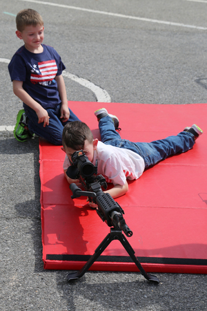NEW YORK - MAY 28, 2017: Young visitors with M249 light machine gun during Fleet Week 2017 in New York