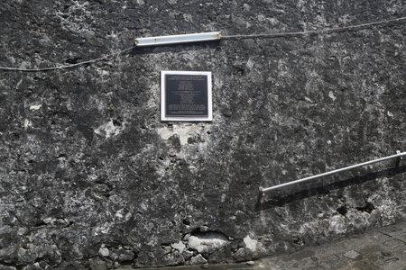 ST. GEORGES, GRENADA - JUNE 12, 2017: Commemorative Plaque for Prime Minister Maurice Bishop at Fort George in Grenada. Maurice Bishop and his ministers executed at Fort George on October 19, 1983.