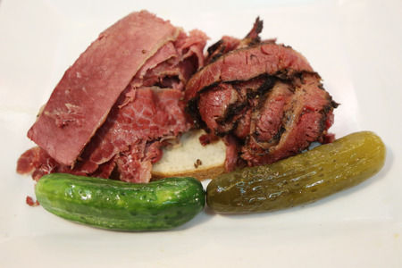 bens: Famous Corned Beef and Pastrami on rye sandwich served with pickles in New York Deli