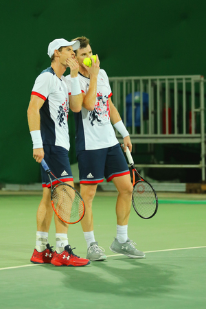 l first: RIO DE JANEIRO, BRAZIL - AUGUST 7, 2016: Tennis players Andy Murray (L) and Jamie Murray of Great Britain in action during mens doubles first round match of the Rio 2016 Olympic Games