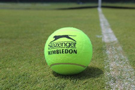 exclusively: NEW YORK - JUNE 29, 2017: Slazenger Wimbledon Tennis Ball on grass tennis court. Slazenger Wimbledon Tennis Ball exclusively used and endorsed by The Championships, Wimbledon