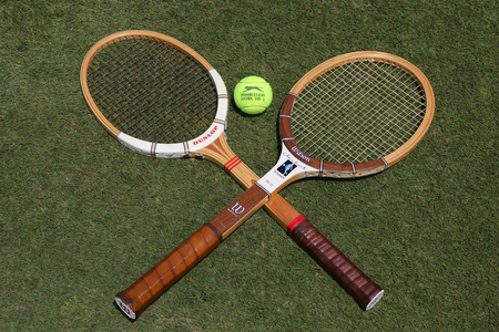 NEW YORK - JUNE 29, 2017:Vintage Tennis rackets and Slazenger Wimbledon Tennis Ball on grass tennis court. Slazenger Wimbledon Tennis Ball exclusively used and endorsed by The Championships, Wimbledon