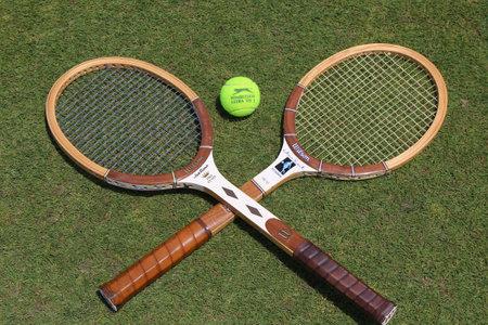 NEW YORK - JUNE 29, 2017:Vintage Tennis rackets and Slazenger Wimbledon Tennis Ball on grass tennis court. Slazenger Wimbledon Tennis Ball exclusively used and endorsed by The Championships, Wimbledon