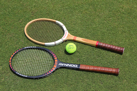 exclusively: NEW YORK - JUNE 29, 2017:Vintage Tennis rackets and Slazenger Wimbledon Tennis Ball on grass tennis court. Slazenger Wimbledon Tennis Ball exclusively used and endorsed by The Championships, Wimbledon