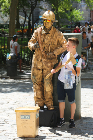 NEW YORK - JULY 16, 2017: Tourist takes picture with firefighter human statue in Lower Manhattan.