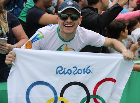 the olympic rings: RIO DE JANEIRO, BRAZIL - AUGUST 7, 2016: Sport fan with Olympic Flag  during Rio 2016 Olympic Games at the Olympic Tennis Center Editorial