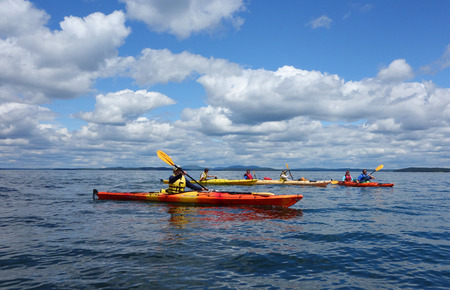 BAR HARBOR, MAINE - JULY 4, 2017: Tourists ride sea kayaks in Bar Harbor. Bar Harbor is a famous summer colony in the Down East region of Maine
